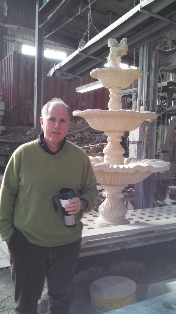 Ralph Petrillo stands next to a hand carved French Limestone fountain created by Petrillo Stone.
