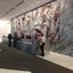 front desk with large painting on white marble wall on 6th avenue